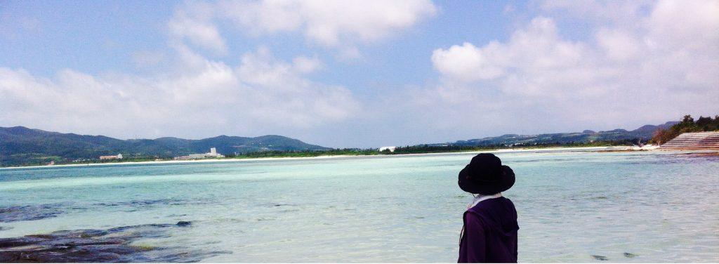 広い空と海をただ見つめる女性