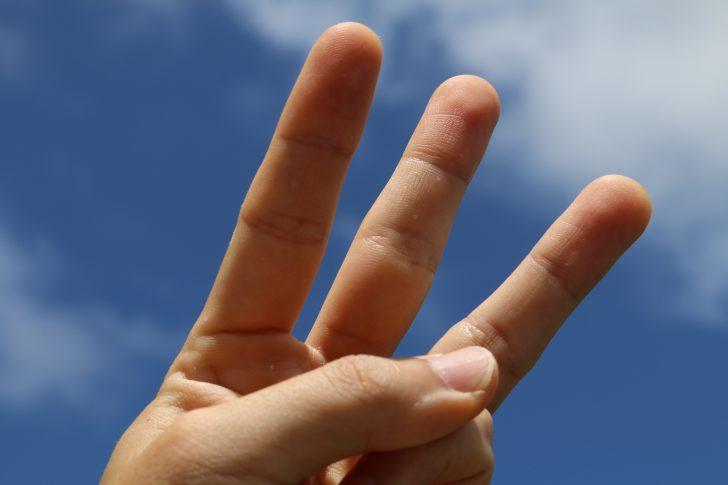 青空を背景に三本指で示す「3つ」