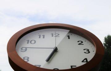 外に置かれて6:45を差す茶色い時計
