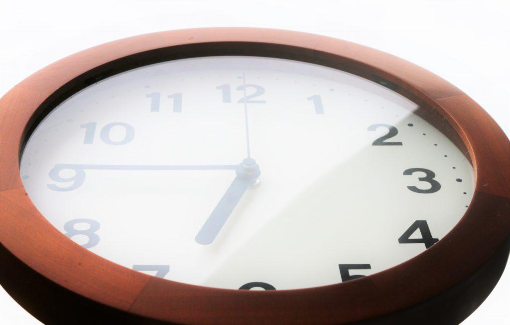 光の中で6:45を指し示す時計
