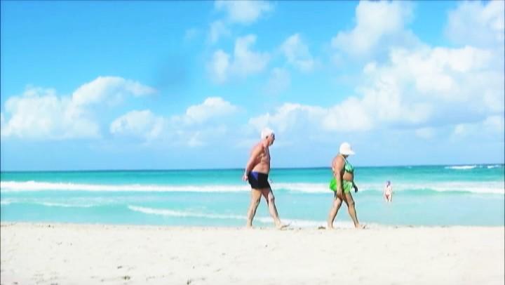 キューバの海岸に老夫婦
