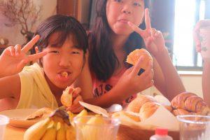 朝食のパンを食べる姉妹