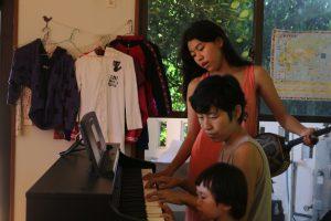 ピアノでバースデーソングを歌う家族