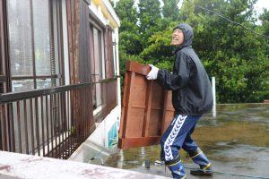 ベランダのさんから雨戸を運び入れる夫