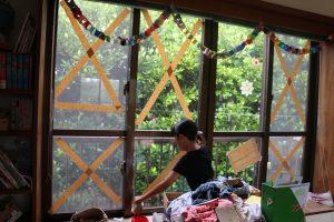 雨戸がない部屋の窓にガードするテープを貼る次女