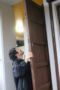 外の雨戸を閉める夫