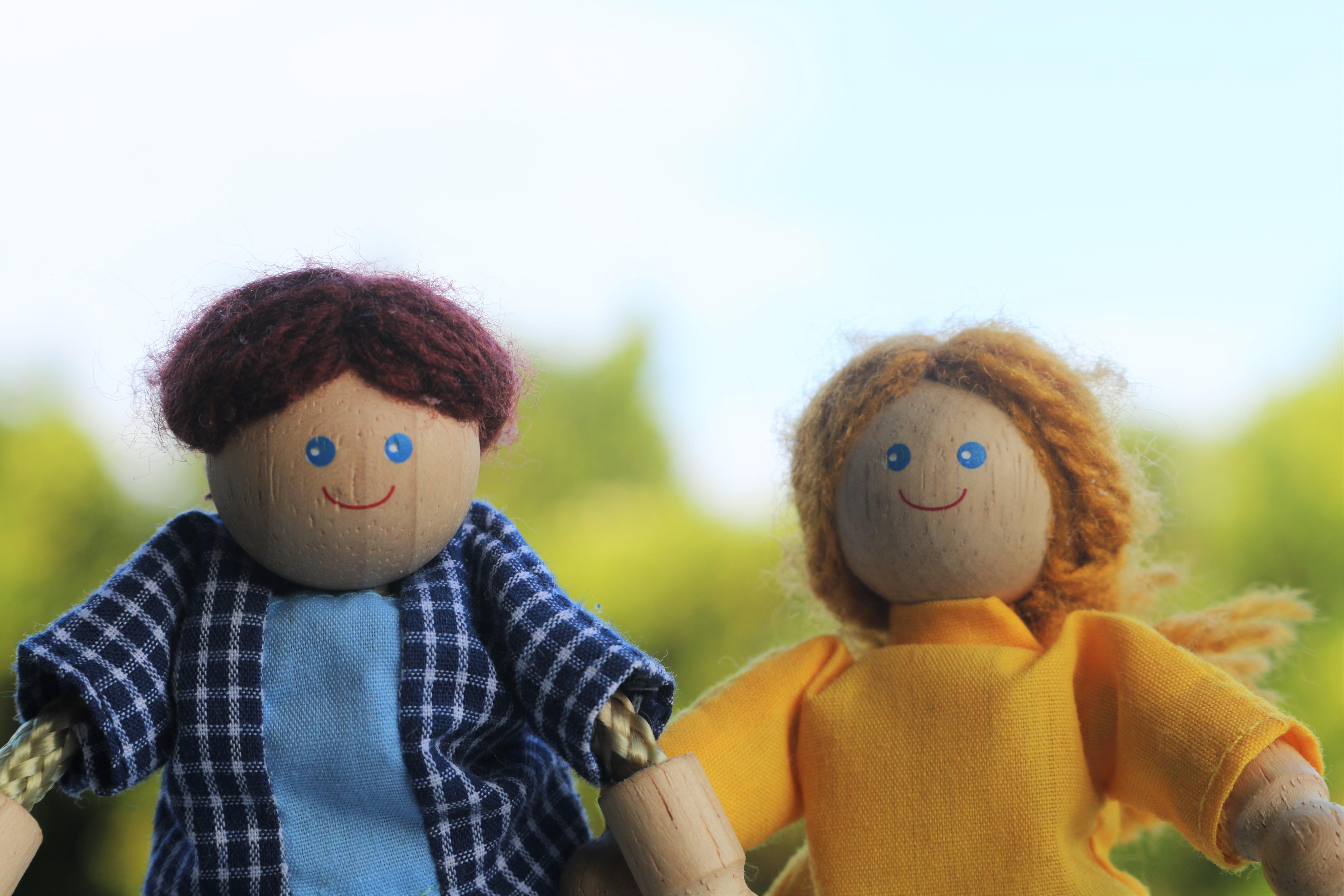 空を背景に笑顔の男女の人形二人