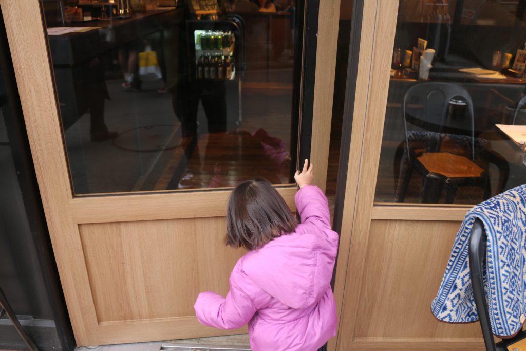 レストランのドアを開ける幼児