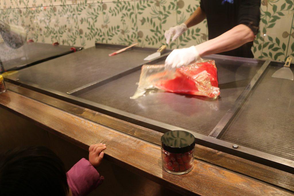 赤と白の材料が交じり合う飴作り