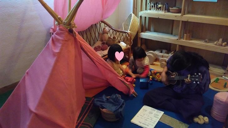 一緒に遊ぶ幼い女の子二人とウクレレを練習する少女