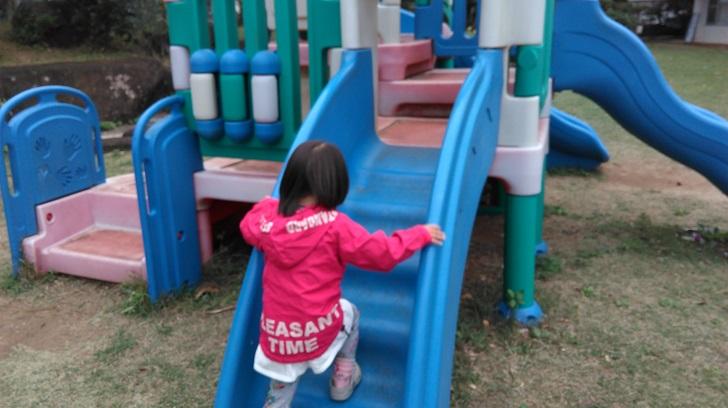 一人で滑り台で遊ぶ女の子