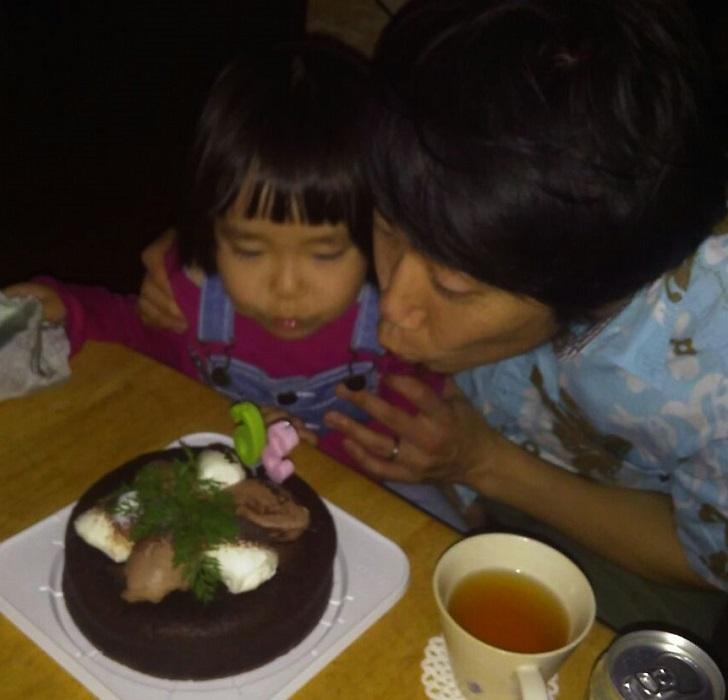 ケーキのろうそくを吹く親子