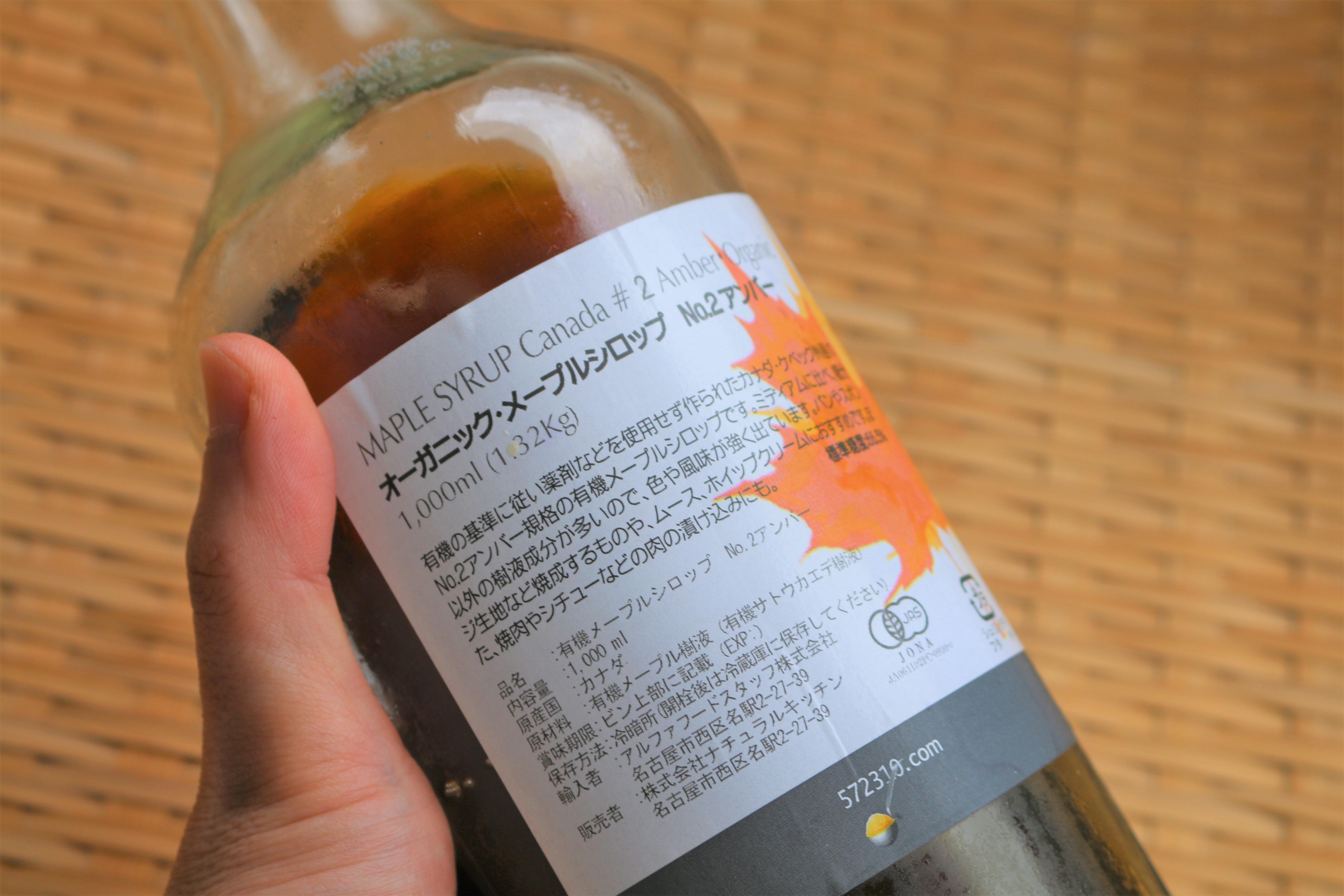 手に持ったメープルシロップの瓶