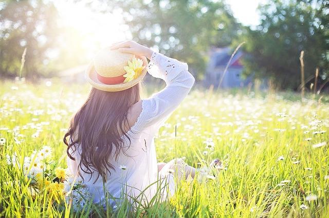 お花畑でひなたぼっこする女性