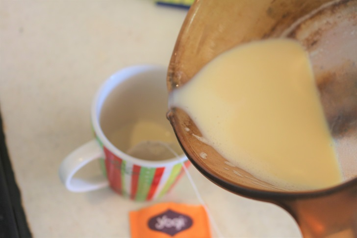 マグカップに鍋から豆乳を注ぐ