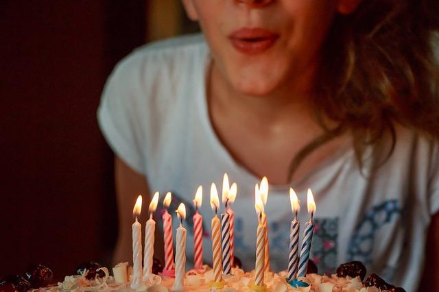 バースデーケーキの上のろうそくを吹き消す女性