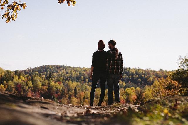 山の上から景色を眺めるカップル