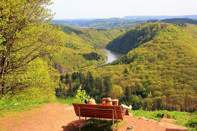 山の上のベンチから下の景色を眺める女性たち