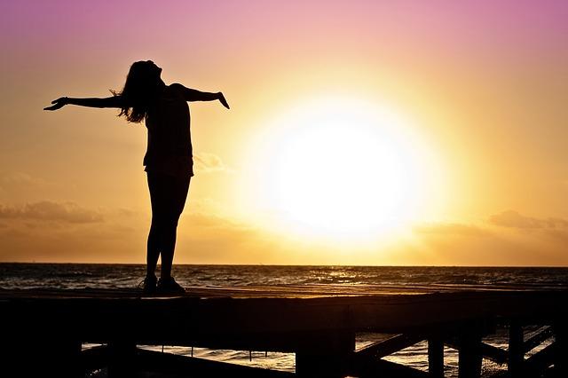 日の出に向かって両手を広げる女性