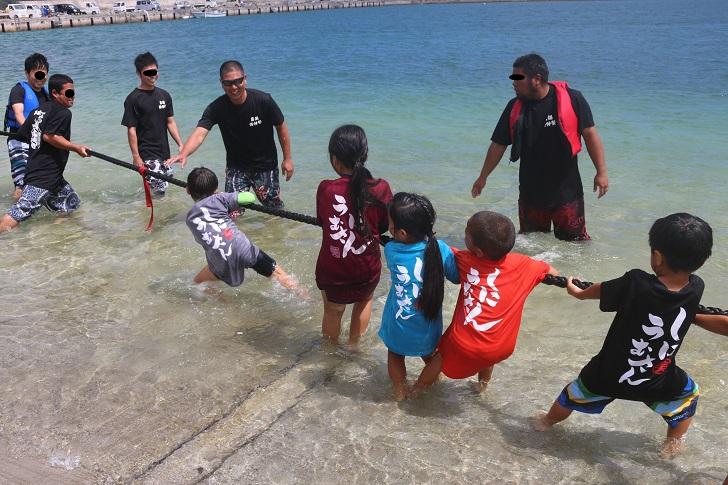 子どもたちが海で綱引き