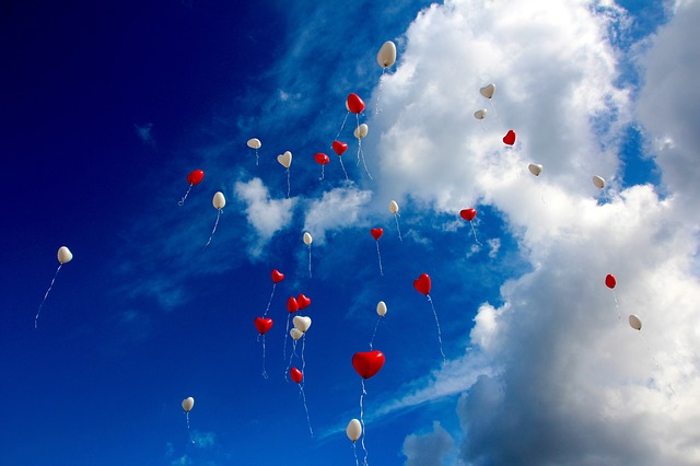 空へ飛んでいくハート型の風船
