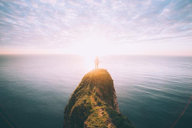 崖の上に立ち朝日を眺める人