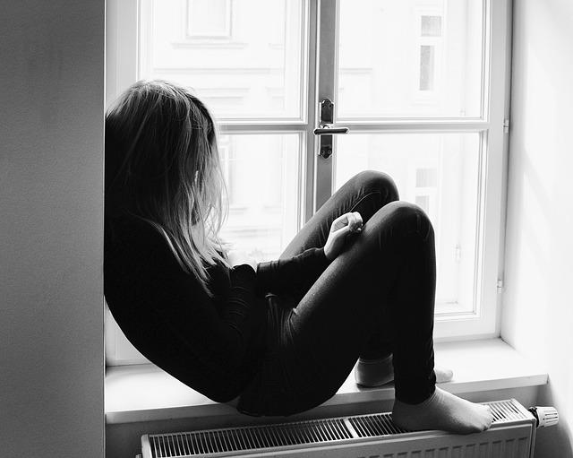 窓辺で落ち込む女性
