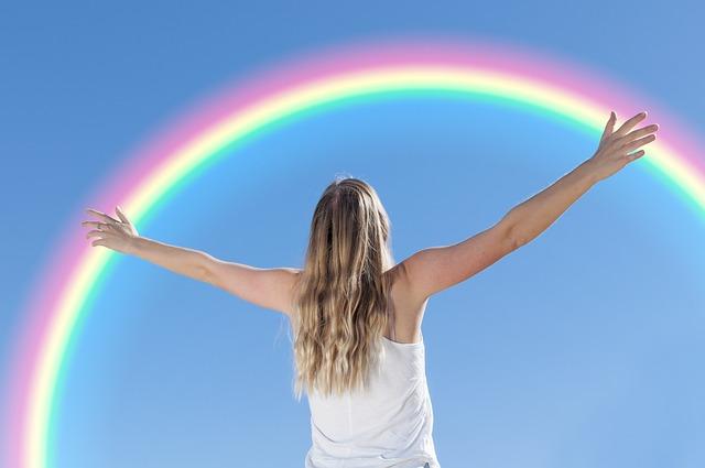 虹に向かって手を拡げる女性