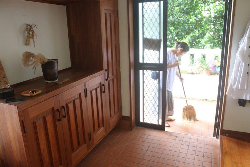 玄関の掃き掃除をする女性